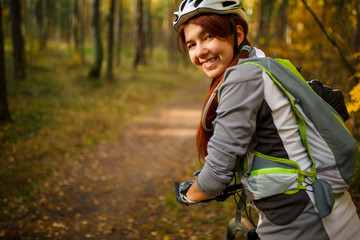 Photo of woman wearing helmet on bicycle in autumn forest