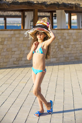 A beautiful young girl wore a lot of hats on her head. Cute funny girl on vacation at summer time.