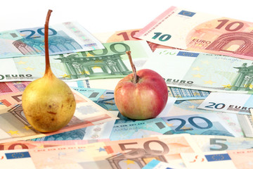a small pile of paper euro bills and an apple with a pear fruit