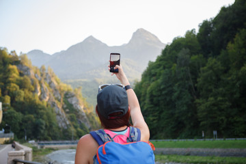 Photo from back of tourist girl photographing mountain