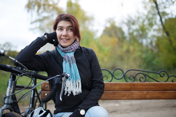 Photo of smiling woman sitting on bench next to bicycle