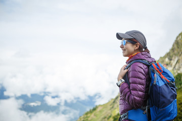 Photo of woman in sunglasses, with backpack background of mountains