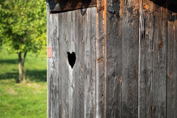 Wooden outdoor toilet with heart on the door.