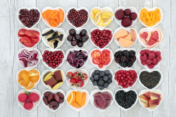 Food for healthy living with fruit, grains, vegetables and pulses in heart shaped dishes on rustic wood background. Health foods high in antioxidants, anthocyanins, vitamins and minerals.