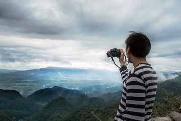 Young man traveler photographing mountain and sunset, Chiangmai Thailand. Alone travel concept.