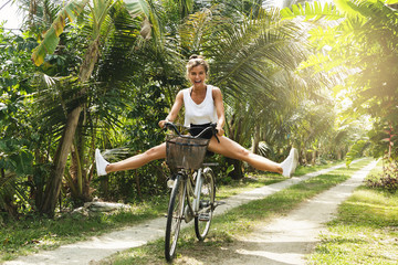 Funny woman riding bicycle in the tropical garden
