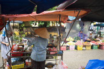 -Selective focus- Unidentified woman with typical vietnamese conical hats sell fresh vegetables and meat skewers on a street market in Hoi An, Vietnam