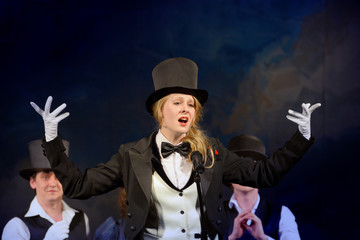 blonde girl in tuxedo and hat singing on stage