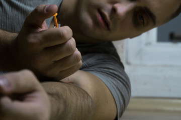 The guy who is addicted to drugs, sits on the floor and injects the next dose with a syringe