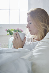 attractive young woman laying in bed and looking at her cup of coffee
