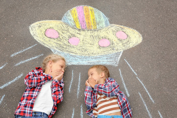 Little boy and girl lying near chalk drawing of alien spaceship on asphalt