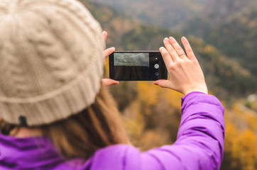 A girl in a lilac jacket takes pictures on a telephone in the mountains, an autumn forest with a cloudy day, free space for text