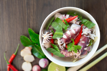 Squid spicy soup (Tom yum) seafood Thailand food in white bowl on brown table