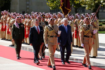 Jordan's King Abdullah and Palestinian President Mahmoud Abbas review Bedouin honour guards at the Royal Palace in Amman