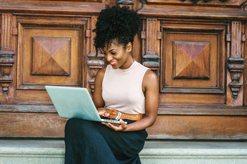 Way to Success. Young African American woman with afro hairstyle wearing sleeveless light color top, black skit, sitting by vintage office door in New York, working on laptop computer, smiling..