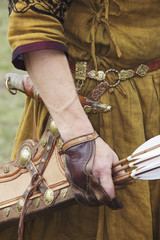 Hand in a beige cloak holds Quiver with arrows in a quiver on a green background.