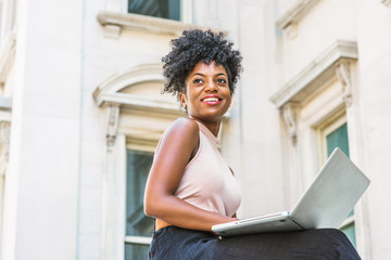 Way to Success. Young African American woman with afro hairstyle wearing sleeveless light color top, sitting by vintage office building in New York, working on laptop computer, looking up, smiling..