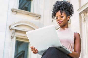 Way to Success. Young African American woman with afro hairstyle wearing sleeveless light color top, sitting by vintage office building in New York, working on laptop computer, looking up, thinking..