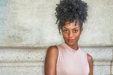Portrait of Young African American Woman in New York. Young black female college student with afro hairstyle wearing sleeveless light color top, standing against vintage wall, looking at you..
