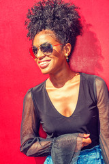 Portrait of Young African American Woman in New York. Young black woman with afro hairstyle wearing long sleeve mesh sheer shirt, sunglasses, standing against red background under sun, smiling..