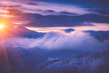 Beautiful sunrise in the winter mountains. Dramatic cloudy over sky. View of foggy hills  and trees covered with rime. Filtered image:cross processed retro effect.