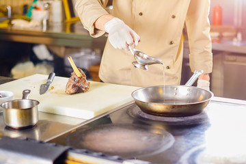 Chef pouring cooking oil into frying pan. Chef in restaurant going to cook the leg of lamb. European cuisine and cooking.