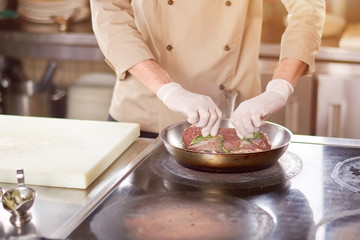 Chef putting on meat on frying pan. Close up cook hands putted meat in frying pan. Male chef cooking meat at work.