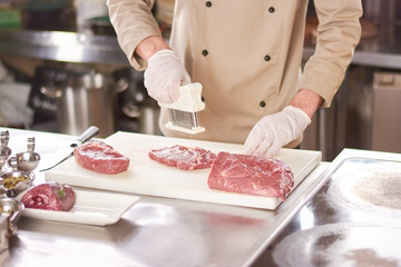 Chef cooking steak at restaurant kitchen. Cook preparing steak from raw beef meat. Chef working at restaurant kitchen.