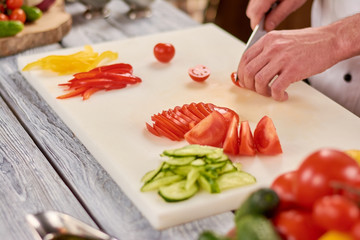 The process of cutting vegetables on white board. Male chef hands chopping fresh vegetables on cutting board. Chef working at professional kitchen.