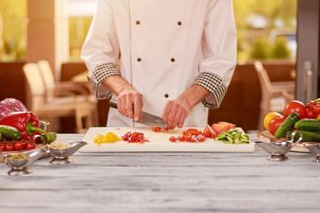 Chef preparing food at professional kitchen. Male chef cutting fresh red tomato at restaurant kitchen.