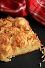 Fresh homemade Apple Pie with almond slivers and red kitchen towel on black background