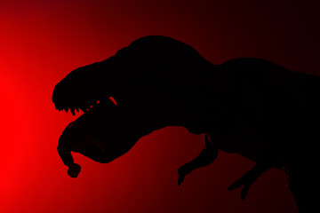silhouette of tyrannosaurus biting a human body on a red background no logo or trademark