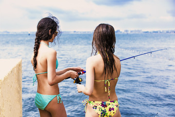 Two young attractive girls in a bikini are fishing for a bait.