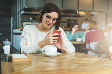 Young happy businesswoman in glasses and sweater is sitting in cafe at table and using smartphone, working.E-learning,online marketing,education.Hipster girl looking on screen of phone,checking email.