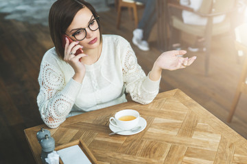 Young businesswoman in glasses and white sweater is sitting in cafe at wooden table and talking on cell phone. Telephone conversations. Hipster girl freelancer discusses working questions over phone.