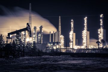 Pump jack and refinery at night.