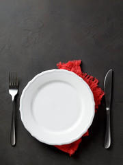 Festive set of knife and fork and white plate on a red napkin on a dark stone slate background, top view, copyspace, vertical image