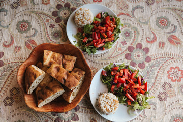 Top view breakfast for two, vegetable salad with rice and cake with sesame seeds on patterned tablecloth