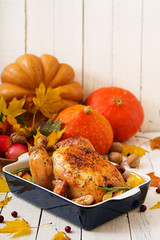 Roasted turkey garnished with cranberries on a rustic style table decorated with pumpkins, orange, apples and autumn leaf. Thanksgiving Day.
