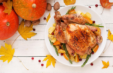Roasted turkey garnished with cranberries on a rustic style table decorated with pumpkins, orange, apples and autumn leaf. Thanksgiving Day. Flat lay. Top view