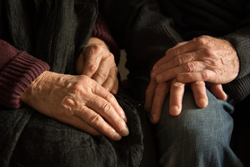 Hands of an old woman and an old man sitting together