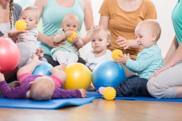Junge Mütter und ihre Kinder spielen gemeinsam im Mutter-Kind-Kurs