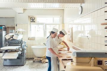 Frauen in der Bäckerei Backstube formen Teil zu Brezeln, die dann gebacken werden