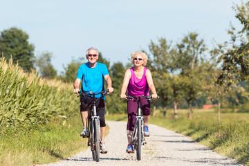 Aktive Senioren, mann und Frau, beim Sport als Fahrrad fahren