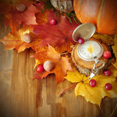 Old watch on autumn yellow leaves and a pumpkin. Concept of time and seasons transition