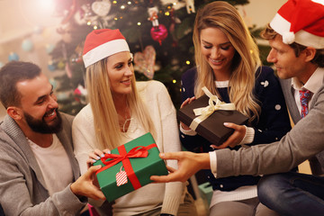 Group of friends with Christmas presents at home