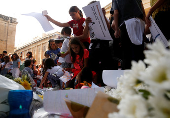Children place flowers, candles and drawings at a memorial for murdered investigative journalist Daphne Caruana Galizia, who was assassinated by a car bomb last Monday, in Valletta