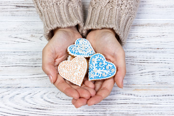 Heart-shaped cookie in woman's hands holiday cookies