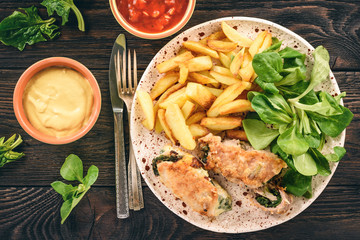 Pork roulades with spinach and cheese filling, served with fried potatoes.