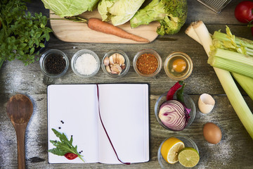 open recipe book with vegetables on wooden background. Top view